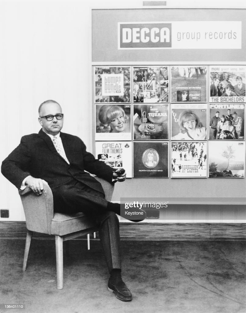 Decca Records producer and A&R man Dick Rowe (1921 - 1986), circa 1965. Behind him is a display of Decca albums by Lulu, The Bachelors and others.