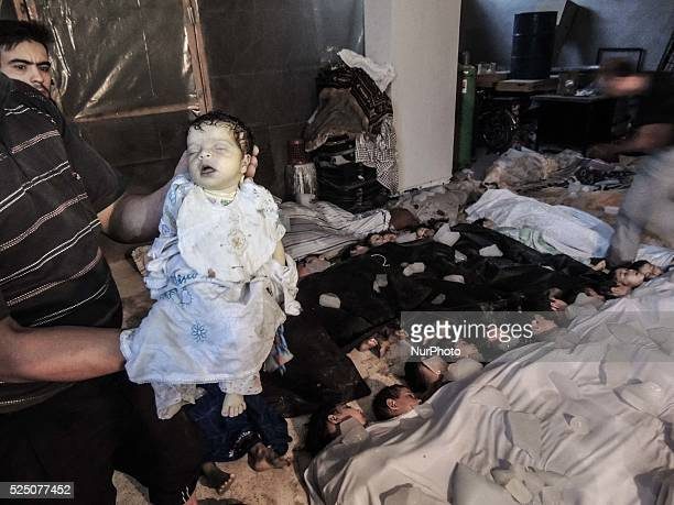 A deceased baby is held in front of a morgue filled with children after that about 1300 people were killed by nerve gas on the Damascus suburb of...