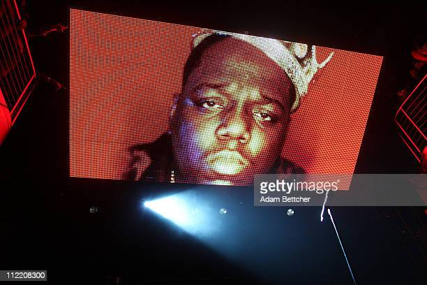 Deceased rapper Notorious BIG is shown on a video screen while Sean Diddy Combs performs on the front of the stage during the kickoff of the Diddy...