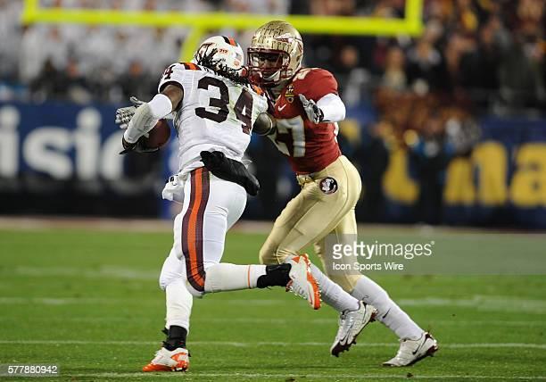 Virginia Tech Hokies running back Ryan Williams stiff arms Florida State Seminoles cornerback Xavier Rhodes on the play at Bank of America Stadium in...
