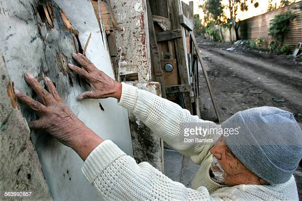December 11 2005 Tijuana Mexico Jose Arias Martinez shows the blast pattern from a tear gas grenade that hit the side of his house His residence...