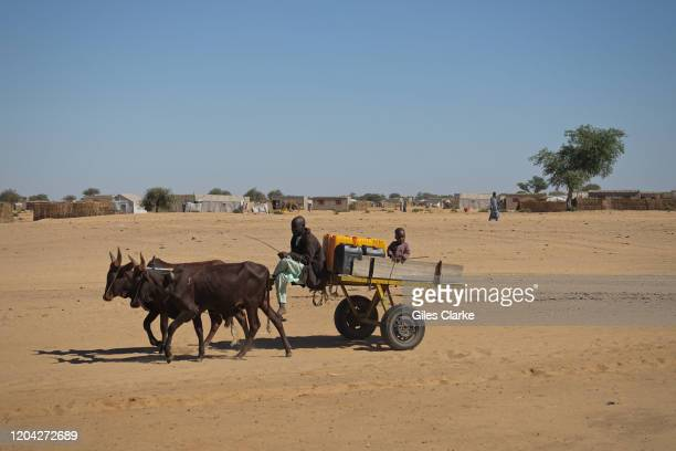 December 11, 2019. A refugee man and child transport water containers by cart and donkey in Awaradi Refugee camp in eastern Niger.
