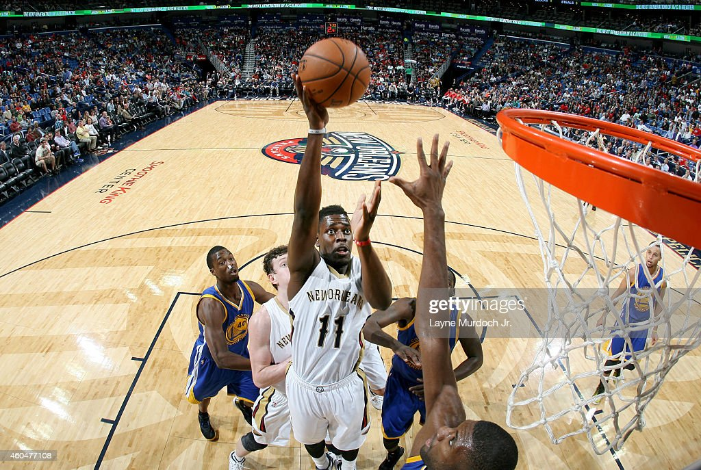 Jrue Holiday #11 of the New Orleans Pelicans goes for the basket against the Golden State Warriors during the game on December 14, 2014 at Smoothie King Center in New Orleans, Louisiana.