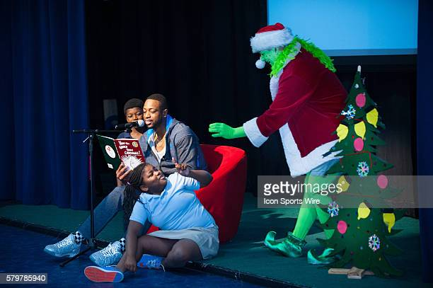 Dwyane Wade reads with Davard Johnson Makayla Refuse of Liberty City Elementary during Wade's World Foundation '3 Under the Tree' holiday event at...