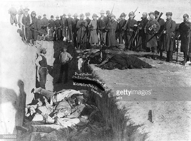 Bodies of Sioux Indians being unceremoniously piled into a mass grave hacked into the frozen Dakota soil after the tragedy at Wounded Knee, South...