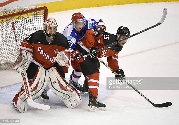 Russia forward Alexander Sharov battles for position with Canada defenceman Darnell Nurse and goalie Zach Fucale during the second period of Russia's...