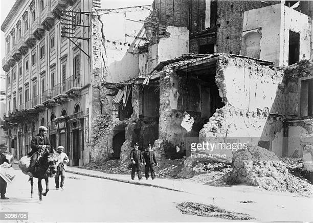 Two policemen walking past a ruined building in Messina Sicily after an earthquake that destroyed half the town and killed over 77000 people