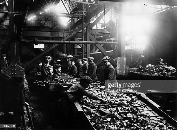 Young boys at work at the troughs used for cleaning coal at a pit in Bargoed South Wales