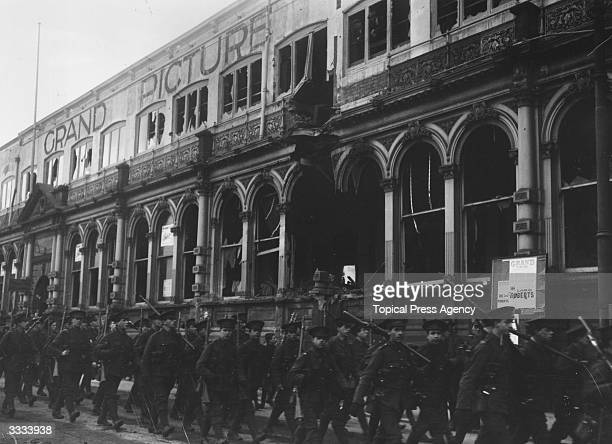 Troops marching past the damaged facade of the Grand Hotel at Scarborough which was shelled during the German bombardment of the city on 16th...