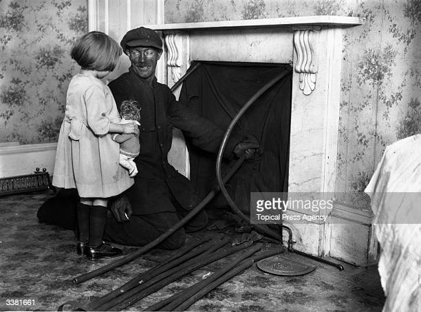 A little girl and a chimney sweep talking while he cleans the chimney