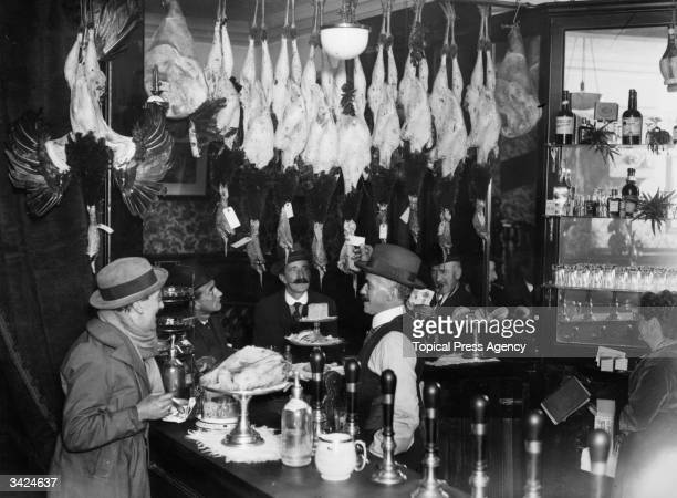 The bar of a public house in the city of London with turkeys and hams on sale for Christmas