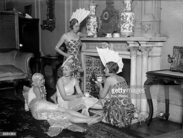Group of girls in their costumes for the Chelsea Arts Ball, having a cup of tea in an opulent sitting room before the festivities. They are dressed...