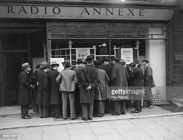 Crowd gathers at Selfridges, London, to read about a demonstration of an early wireless machine used for sending messages.