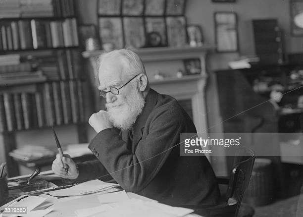 Irish dramatist essayist critic and pamphleteer George Bernard Shaw working at his desk