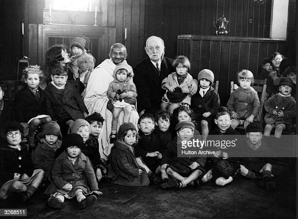Indian thinker statesman and nationalist leader Mahatma Gandhi with George Lansbury and a group of children at Kingsley Hall in the East End of...