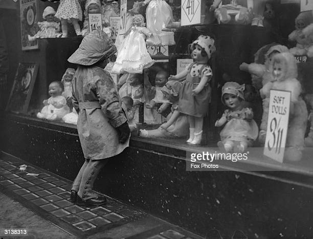 Girl in a raincoat gazes into a shop window in Holborn, London, at a Christmas display of dolls.
