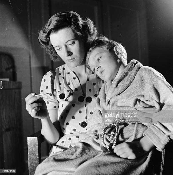 Model Vera Dunlop taking the temperature of her sick son.