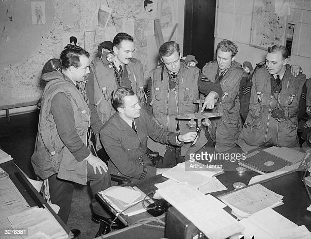 A Royal Air Force Coastal Command crew at debriefing the sergeant is using a model of a Dornier bomber to explain how he carried out his attack on a...