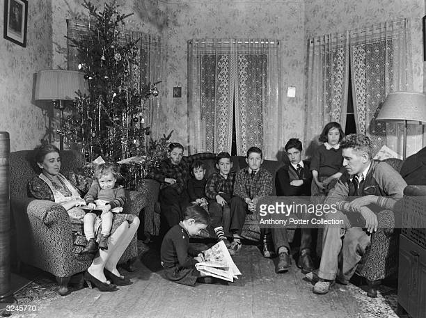 Family portrait of John Kelly who worked in a Navy yard in South Boston Massachusetts sitting with his wife and eight children in their living room...