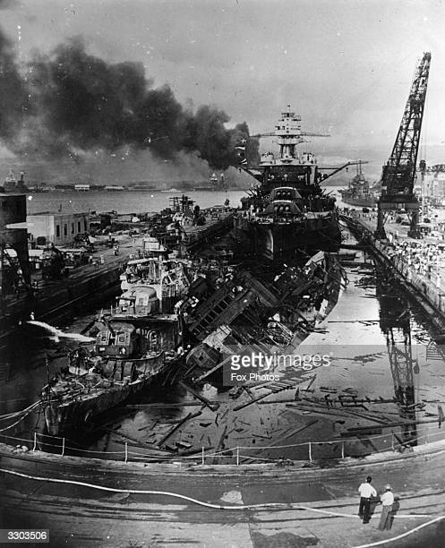 The jumbled mass of wreckage in front of the battleship USS Pennsylvania constitutes the remains of the destroyers USS Downes and USS Cassin, bombed...