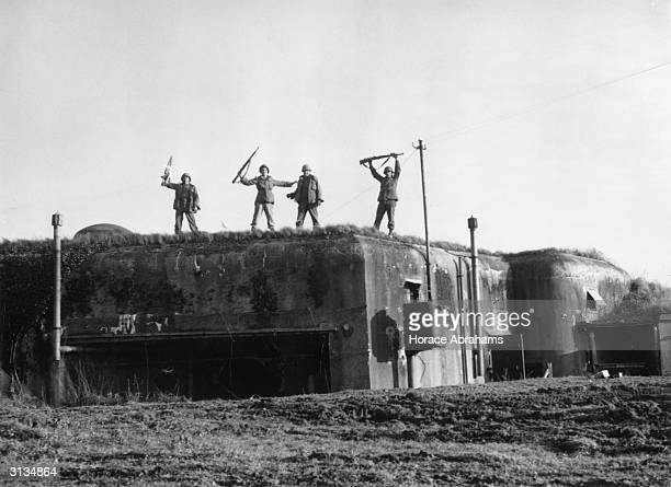 Four soldiers of the US 7th Army stand triumphantly atop one of the captured Maginot forts at Koenigsbruck during their World War II advance toward...