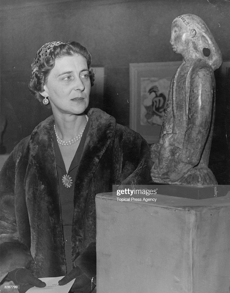 Marina, Duchess of Kent (1906 - 1968), daughter of Prince Michael of Greece, visits the Royal Society of British Artists Exhibition at the Suffolk Street Galleries, London. She is viewing 'The Fledgeling' by Folkard.
