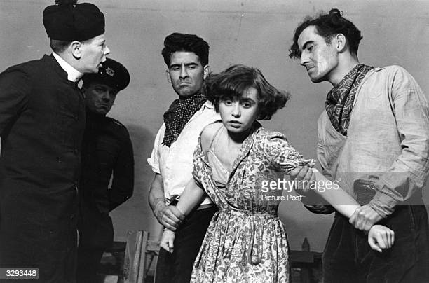Scene from the show Cock A Doodle Dandy A young woman being attacked by a group of men including a priest Original Publication Picture Post 5573...