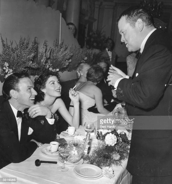 Orson Welles talks to husband and wife Frank Sinatra and Ava Gardner at a charity function at the Empress Club, London, organised by the Variety Club...