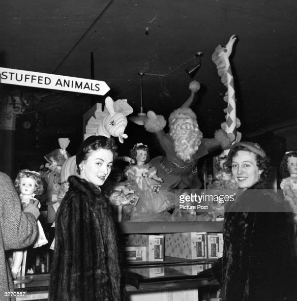 Two employees of Pan American Airways in the toy department of Macy's department store in New York City at Christmas during their world trip a...