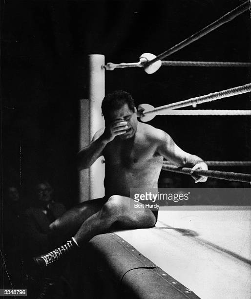 Wrestler Milo Popocopolis sits outside the ring in misery after he was thrown by Vic Hesselle during an International Free-Style Wrestling contest...