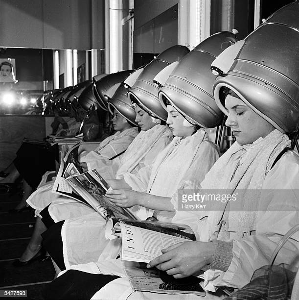 Women relax underneath the hairdryers in a selfservice hairdressing salon