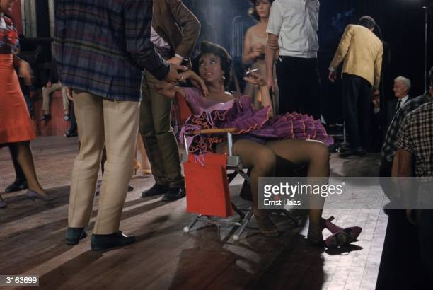 Rita Moreno collapses in a chair for a quiet smoke on the set of the musical 'West Side Story' directed by Robert Wise and Jerome Robbins