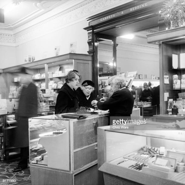 Two women inspecting pens at the stationary counter in Gorringe's department store just up the road from Buckingham Palace London Another customer...