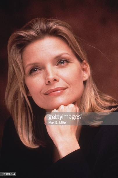 Headshot of American actor Michelle Pfeiffer smiling while resting her chin on her hand