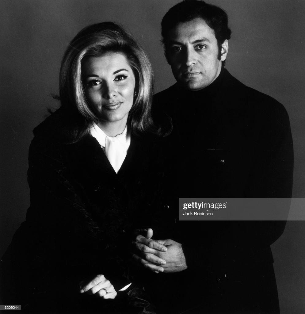 Studio portrait of Indian conductor Zubin Mehta posing beside his wife, Nancy Kovack. She wears a white ascot, and Mehta wears a dark peacoat and turtleneck.