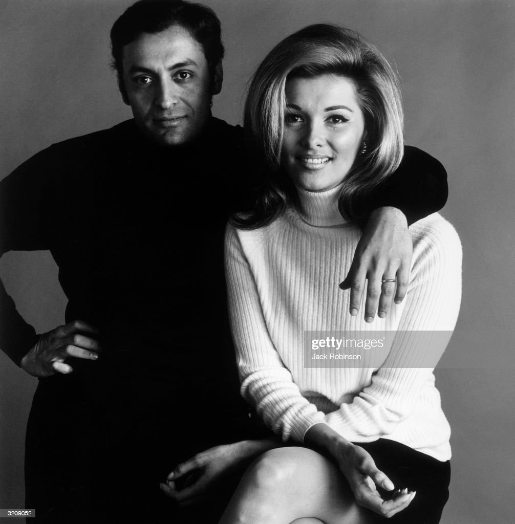 Studio portrait of Indian conductor Zubin Mehta posing with his arm around the shoulder of his wife, Nancy Kovack. She wears a white turtleneck sweater, and Mehta wears a dark turtleneck.