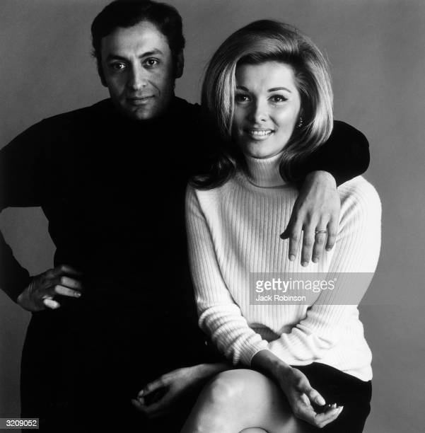 Studio portrait of Indian conductor Zubin Mehta posing with his arm around the shoulder of his wife Nancy Kovack She wears a white turtleneck sweater...