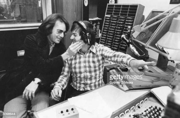American pop singersongwriter Neil Diamond affectionately squeezes the cheeks of BBC Radio 1 disc jockey Tony Blackburn while he is broadcasting in...