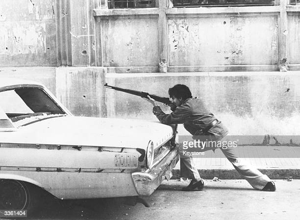 A man aiming a rifle over the back of a car on a street in Beirut Lebanon during the country's civil war