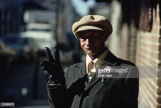 In New Orleans an elderly man wearing black leather gloves and a large flat cap gives a V for victory sign In his buttonhole he wears a small stars...