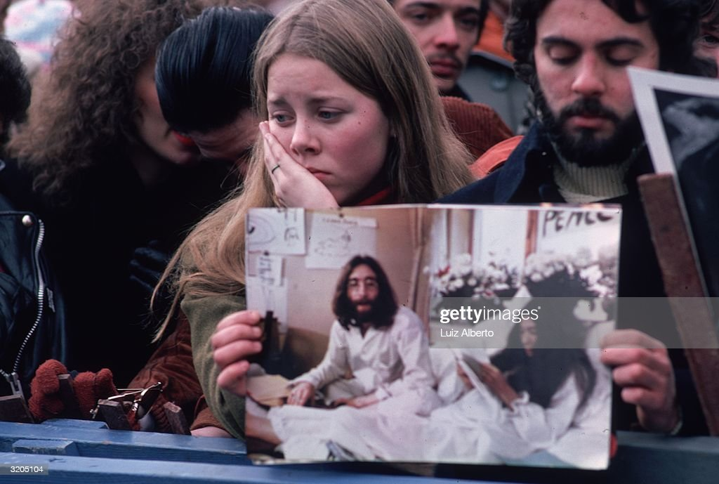 A man and woman among the crowd in Central Park, New York, who have gathered to mourn the death of John Lennon. The man holds a picture of Lennon and Yoko Ono in bed during one of their 'love-in' peace protests.