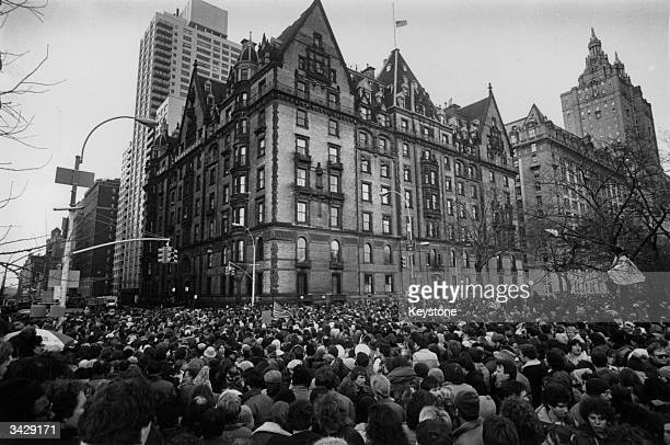 Crowds gathering outside the home of John Lennon in New York after the news that he had been shot and killed. A flag flies at half-mast over the...