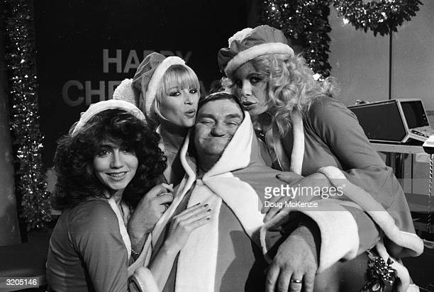 English comedian Les Dawson and glamorous assistants all in santa costumes for his Christmas TV show