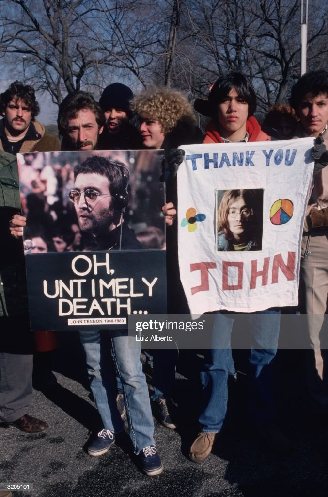 People gathered at Central Park, New York, to mourn the death of John Lennon. They are holding pictures of Lennon.