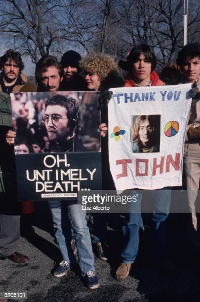 People gathered at Central Park New York to mourn the death of John Lennon They are holding pictures of Lennon