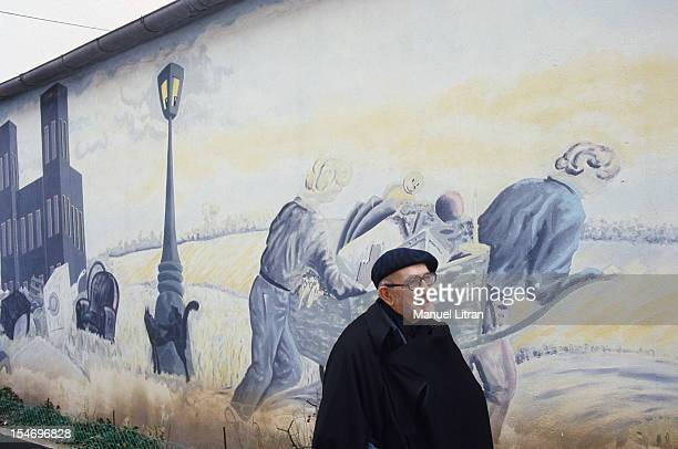 December 1985 Abbe Pierre celebrates Christmas with the Emmaus community here the abbot walking along a mural representing the ragpickers of Emmaus...