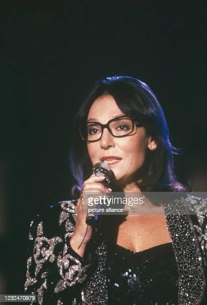 December 1987, North Rhine-Westphalia, Cologne: The singer Nana Mouskouri at a TV appearance on Photo : Horst Galuschka Photo: Horst Galuschka/dpa