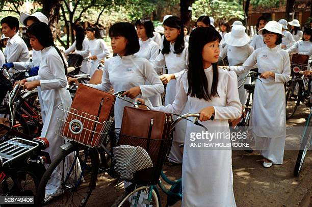December 1991 Ho Chi Minh City Vietnam School girls in traditional Vietnamese dresses called Ao Dai leaving school in Saigon Photo Credit ANDREW...