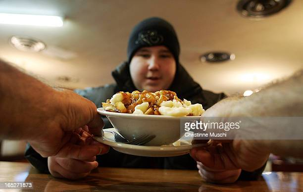 December 2 200413 yr old Jonathan Trudel waits for his plate of poutine at the Green Spot in Montreal on December 2 2004 For story by Miro National