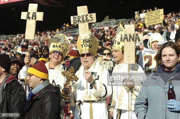 Three Saints fans dressed as Saints / Popes /Bishops hold a sign that says 'LaBreesiana' The New Orleans Saints defeated the Washington Redskins 3330...